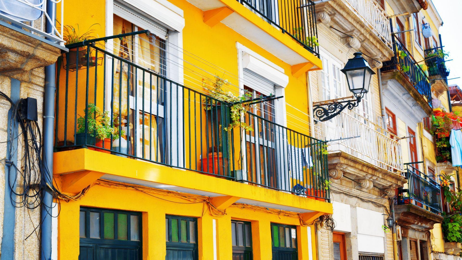 Spalvoti namų fasadai kontrastingame Porte